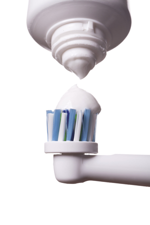 bristles: Close up of electric toothbrush with blue bristles and tube with paste bubbled at its opening on white background Stock Photo