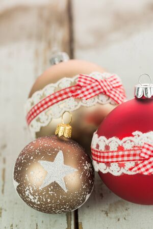 Three colorful decorated Christmas baubles on rustic wood with copy space to celebrate the Xmas holiday season
