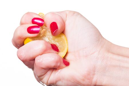 Hand with manicured nails painted a deep glossy red squeeze lemon on white background
