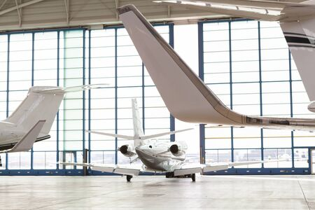 Small Passenger Airplane Leaving Brightly Lit Hangar Through Opening Glass Doors with View Past Tails of Aircraft at Airport