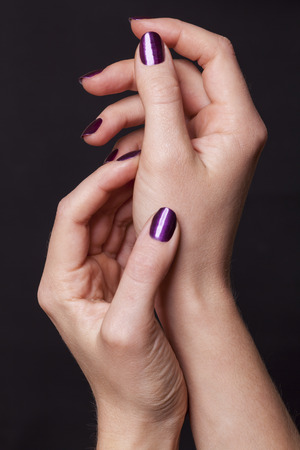 fingernail: Close up of crossed over female hands decorated with purple fingernail paint over black Stock Photo