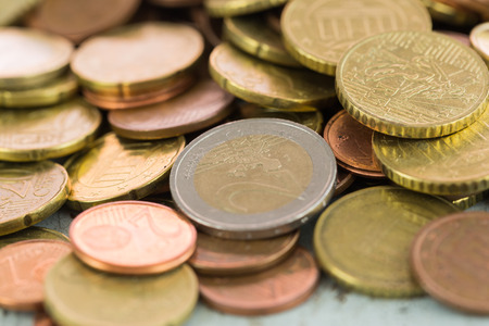 denominations: Heap of assorted Euro coins in different denominations in a vertical shallow dof view in a full frame financial background