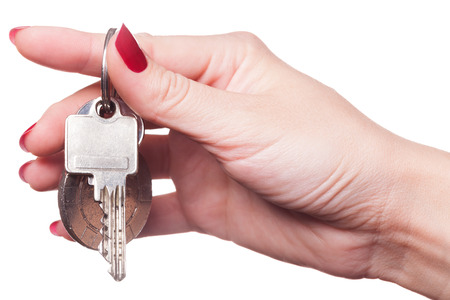 Close up of manicured fingers painted a deep glossy red curling around set of car keys Stok Fotoğraf