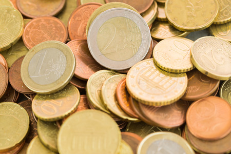 Heap of assorted Euro coins in different denominations in a vertical shallow dof view in a full frame financial background
