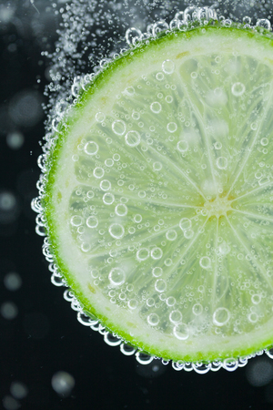 effervescence: Close-up of single green lime slice falling into carbonated water with bubbles on black background. Refresher drink concept