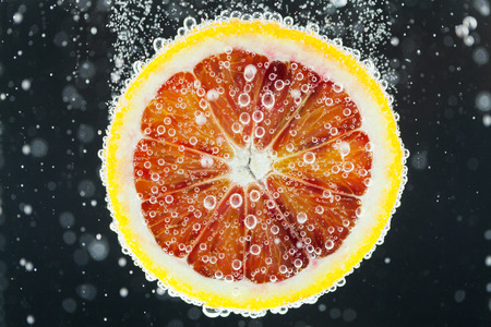 Close-up of blood orange slice diving into carbonated water with bubbles on black background. Refresher drink concept Stok Fotoğraf
