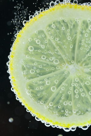 Close-up view of lemon slice under carbonated water with bubbles, refresher concept on black background