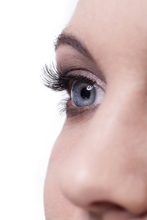 Nahaufnahme von einzelnen menschlichen weiblichen blauen Auge mit langen dunklen Wimpern und eine Nase auf weißem Hintergrund