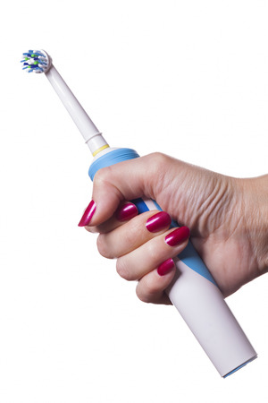 Hand with manicure holds single blue electric toothbrush against white background Stok Fotoğraf