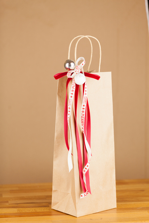 Close-up of Christmas gift bag of kraft paper with red and white ribbon decoration, vertical on brown background