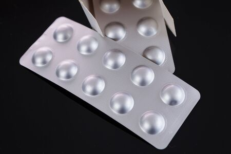 Silver blister pack of small pills together with the a box with additional packs showing through the open lid over a black background in a healthcare concept Stok Fotoğraf