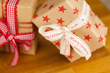 Close up vertical shot of several present boxes in kraft paper decorated with ribbons and red star pattern, on wooden surface