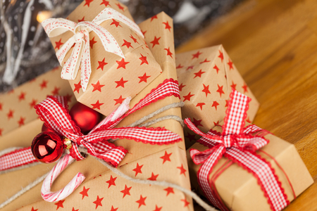 Close-up composition of Christmas present boxes of kraft paper with ribbons, decorations and stars pattern
