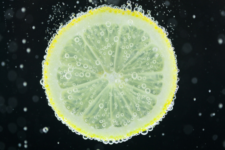 effervescence: Close-up view of lemon slice under carbonated water with bubbles, refresher concept on black background