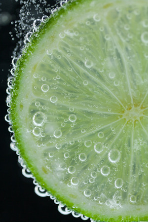 Close-up of single green lime slice falling into carbonated water with bubbles on black background. Refresher drink concept