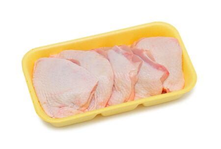 Frozen chicken in a plastic tray, isolated on a white background photo