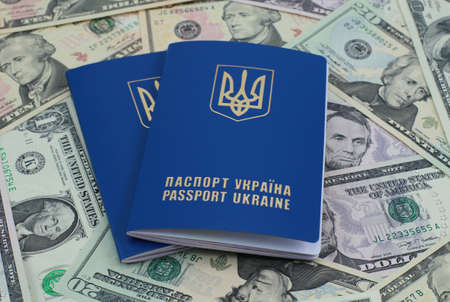 Two Ukrainian international passports on the bank notes background photo