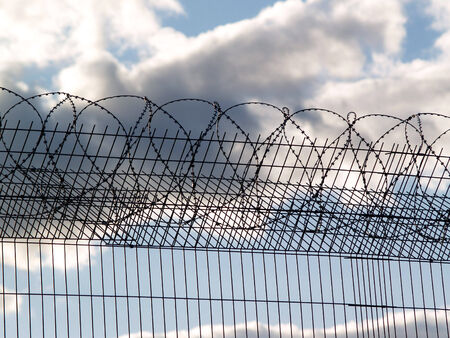 Prison fence with barbed wire on the cloudy sky background photo