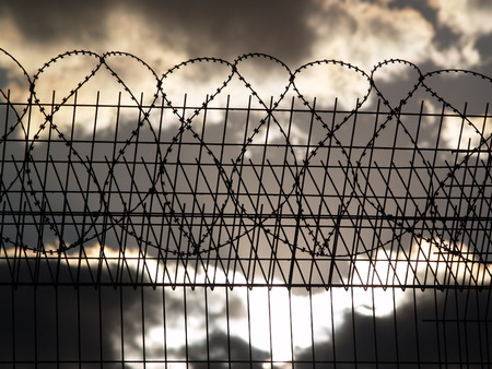 prison fence: Prison fence with barbed wire on the cloudy sky background