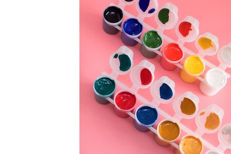 Multi-colored paint in cans on pink background. Palette of colors. Concept - creativity and school theme.
