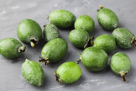 Green feijoa fruits on gray concrete background table. Tropical fruit feijoa. Set of ripe feijoa fruits. Copy space