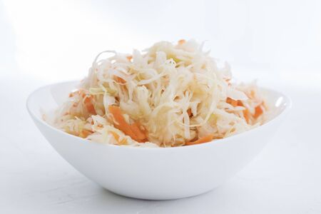 Sauerkraut in a white plate. Homemade sauerkraut with carrot . Fermented food. Natural probiotic. Copy space for text Standard-Bild