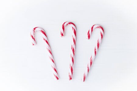 Composition of three Christmas candy canes on a white wooden background. Top view. Place for text.
