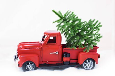 Green spruce in a red Christmas truck on a white background. Concept - greeting card for Christmas and New Year, holiday delivery. Copy space Stock Photo - 133333399