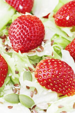 Diet summer salad with strawberries, leaves iceberg lettuce, and seeds, a light snack, healthy food. Copy cpace