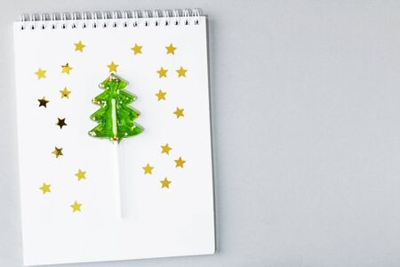 Lollipop caramel in the form of a Christmas tree on a white notebook with stars on a gray background. The concept of Christmas sweets for children. Copy space