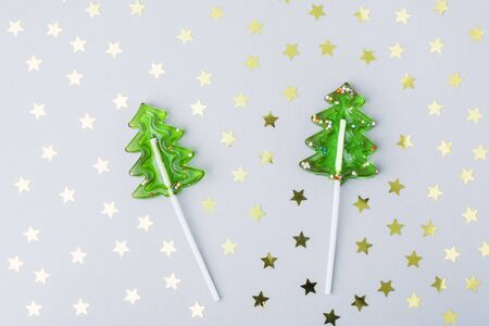 Lollipops caramel in the form of a Christmas tree on a gray background with stars. The concept of Christmas sweets for children, creative christmas tree. Copy space
