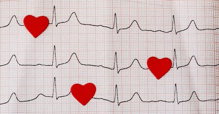 Red hearts on a cardiogram, a heartbeat symbol. Close up of an electrocardiogram in paper form. Healthcare and medical concept. Copy space Reklamní fotografie