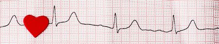 Red heart on a cardiogram, a heartbeat symbol. Close up of an electrocardiogram in paper form. Healthcare and medical concept, banner. Copy space Reklamní fotografie