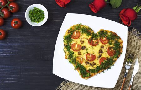 Valentines Day food. Heart shaped pizza with greens, on a white plate, on burlap, on a dark background, next to red roses and cherry tomatoes. Top view. Copy space