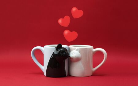 Mugs in the form of cats in love on a red background with hearts. Concept valentines day postcard, banner. Copy space