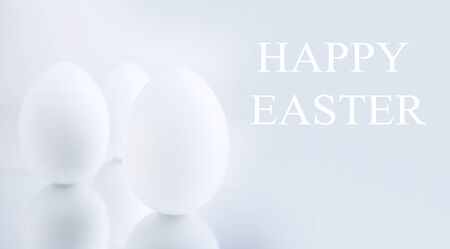 Chicken eggs painted white on a gray background are reflected on a mirror surface. Creative greeting card Happy Easter. Copy space