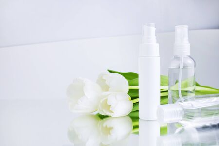 Skin care products white bottles of cosmetic product on white gray background, next to tulips. Facial cleanser and cream, moisturizer, lotion. Spring season cosmetics advertisement. Copy space Stock Photo