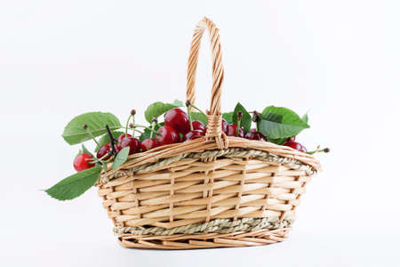 Ripe cherry in a wicker basket is isolated on a white background. Summer harvest of cherries. Stockfoto