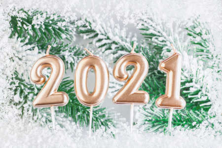 Text 2021 in a snow frame against the background of the branches of a Christmas tree. Christmas and New Year concept. Postcard. Copy space Archivio Fotografico