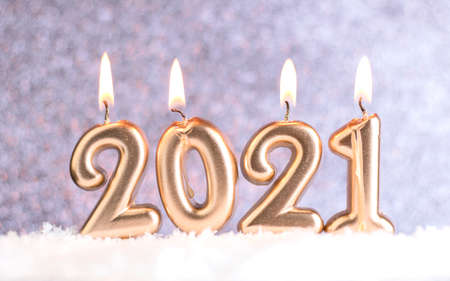 Text 2021, burning melting candles in the snow, on a blurred silver background with bokeh. Christmas and New Years concept. Postcard. Copy space
