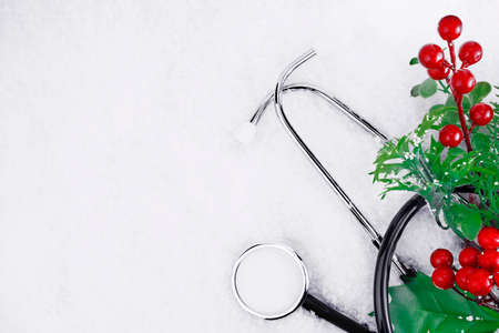Medical stethoscope on a snowy background near a Christmas branch. Medical concept for Christmas or New Year. Flatly. Copy space Reklamní fotografie