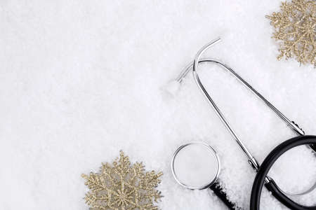 Medical stethoscope on a snowy background near snowflakes. Medical concept for Christmas or New Year. Flatly. Copy space