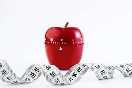 Red kitchen timer in the form of a red apple on a white background, near a measuring tape. Healthy dietary food concept. Copy space