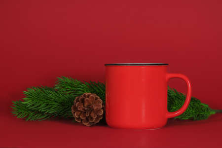 Red mug with coffee, tea or cocoa on a red background with branches of a Christmas tree fir and a pine cone. Christmas or New Year concept. Copy space