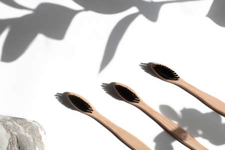 Bamboo toothbrushes isolated on white concrete background with plant shadows. The concept of personal hygiene, dentistry, zero waste, environmental friendliness. Copy space