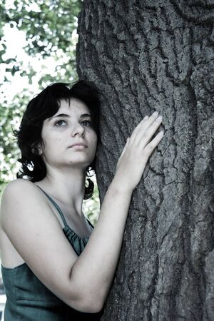 The beautiful girl has embraced a tree photo