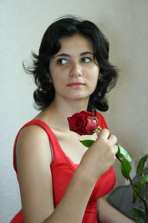 The beautiful girl holds a scarlet rose photo
