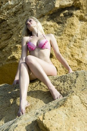 The beautiful girl sits on yellow stones photo