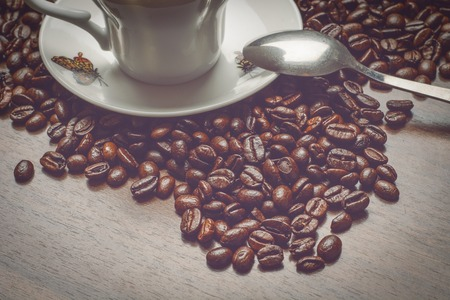 coup: Coup of coffe alongside with coffe beans on wooden table alongside with spoon