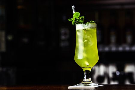 Green cocktail with mint and lemon on the bar. Cocktail served